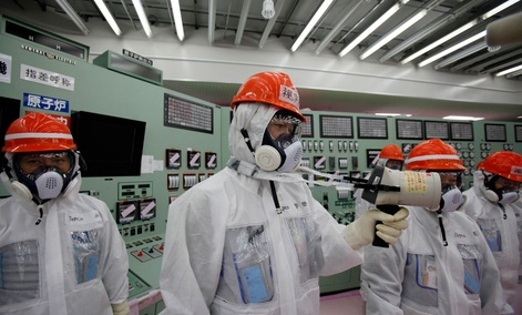 A staff member of the Tokyo Electric Power Co. measures radiation levels inside the central control room of the No. 1 and No. 2 reactors at the Fukushima Dai-ichi nuclear power plant.