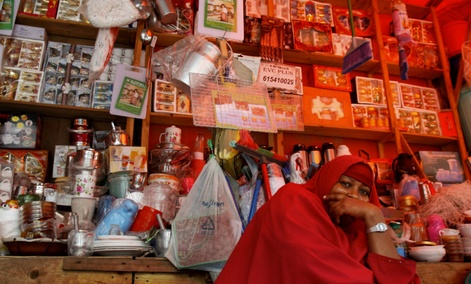 A Somali shopkeeper sells kitchen utensils sits in her shop in Mogadishu, Somalia.