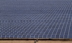Indian workers walk past solar panels at the 200 megawatt Gujarat Solar Park.