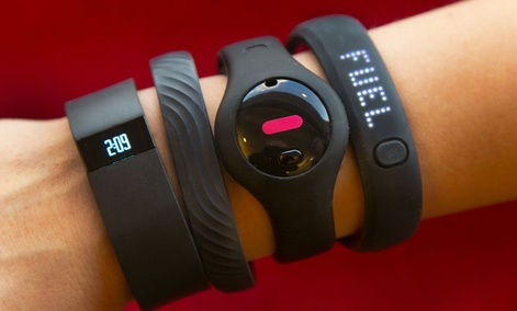 Four fitness trackers are worn, including the Fitbit Force and Nike FuelBand SE.