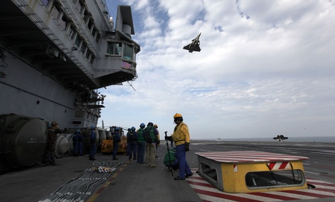 A French military plane flies over the USS Harry S. Truman aircraft carrier in the Gulf of Oman.