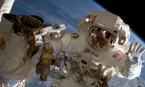 American astronaut Clay Anderson waving during a spacewalk outside the International Space Station.