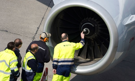 Members of ground staff inspect an engine of a Lufthansa aircraft at Tegel airport in Berlin.