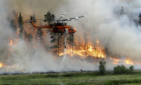 A helicopter drops water as it assists in firefighting efforts at the Taylor Creek fire 25 miles southeast of Ashland, Montana.