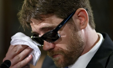 Travis Fugate, a member of the Kentucky National Guard who was blinded by an IED attack in Iraq, wipes his eyes as he testifies on before Congress on May 29, 2014.
