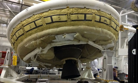 A saucer-shaped test vehicle holding equipment for landing large payloads on Mars in the Missile Assembly Building at the U.S Navy's Pacific Missile Range Facility.