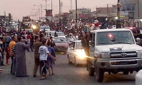 ISIS militants parade down a main road in Mosul, Iraq.