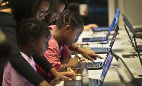 Black Girls Code workshop volunteers work with students during an app building session at Google.
