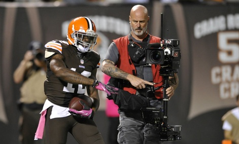 Cleveland Browns wide receiver Josh Gordon (12) celebrates beside a television cameraman during an NFL football game against the Buffalo Bills.