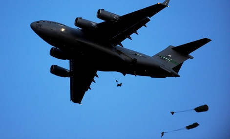 Paratroopers jump from a C-17 in an exercise.