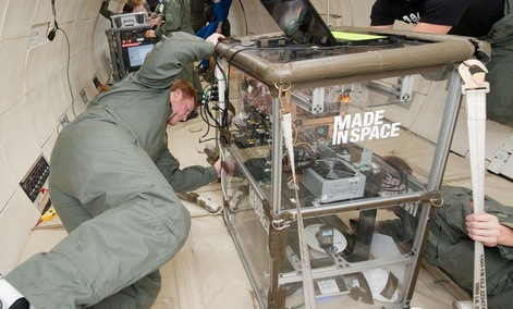 Two people monitoring the performance of extruders inside the Made In Space experiment box during a microgravity portion of flight aboard a modified Boeing 727 from the Zero G Corporation.