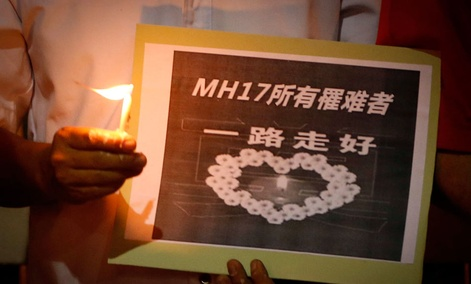 "A man holds a sign which reads "" MH17 Victims Rest In Peace"" during a candlelight vigil for the victims who were on board the Malaysia Airlines jetliner."