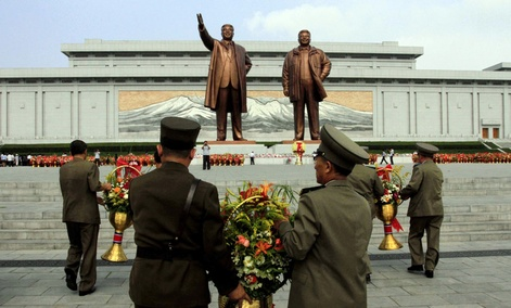 North Korean soldiers bring flowers to the statues of the late leaders Kim Il Sung, left, and Kim Jong Il in Pyongyang, North Korea.