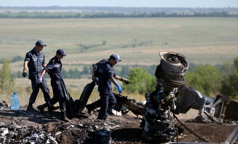 Ukrainian Emergency workers carry a victim's body in a plastic bag at the crash site of Malaysia Airlines Flight 17.