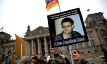 Protesters hold posters of former National Security Agency member Edward Snowden in front of the German parliament building.
