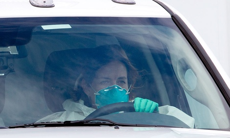 A woman in protective clothing drives an ambulance after departing Dobbins Air Reserve Base in Marietta., Ga., en route Emory University Hospital, carrying Ebola patient Dr. Kent Brantly.