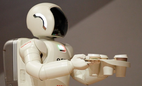 Honda Motors' humanoid robot ASIMO carries coffee.