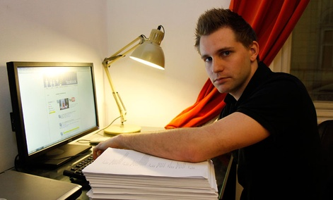 Austrian student Max Schrems sits with files about his activities on his Facebook account that Facebook handed over to him, in Vienna, Austria.