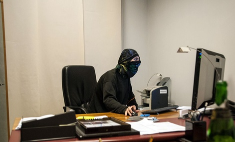 A masked pro-Russian activist sits in front of a computer inside a room.