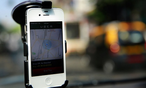 A smartphone is mounted on the glass of an Uber car