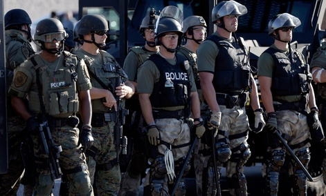 Police in riot gear watch protesters in Ferguson, Mo. on Wednesday, Aug. 13, 2014.