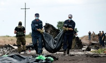 Ukrainian emergency workers carry a victim's body in a bag, at the crash site of Malaysia Airlines Flight 17 near the village of Hrabove, eastern Ukraine
