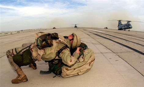 Deployed from USS Bataan and arriving in Afghanistan with a heavy backpack, a Marine with the 26th Marine Expeditionary Unit (Special Operations Capable), dons his backpack by laying his back on it.