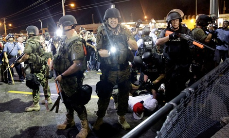 A man is arrested as police try to disperse a crowd during protests in Ferguson, Mo.