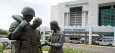 Three statues portraying a wounded soldier being helped, stand on the grounds of the Minneapolis VA Hospital.