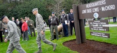 Army Col. Thomas Brittain, left, and Air Force Col. Kenny Weldon walk away from the new headquarters sign after a ceremony marking attainment of initial operational capability for Joint Base Lewis-McChord.
