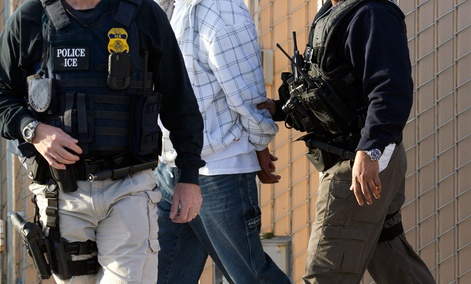 In this March 30, 2012 photo, Immigration and Customs Enforcement agents take a suspect into custody.