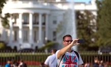 A man takes a selfie with the White House in Washington, DC.