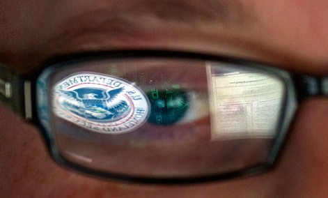 A reflection of the Department of Homeland Security logo in the eyeglasses of a cybersecurity analyst at the watch and warning center of the Department of Homeland Security's secretive cyber defense facility in Idaho Falls, Idaho.