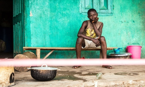A youth under quarantine sits behind a cordon outside his house in Moyamba town on the outskirts of Freetown, Sierra Leone.