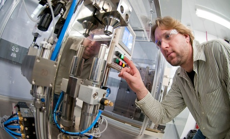 Process engineer Bryant Polzin fills an 18650 lithium-ion battery cell with electrolyte using semi-automated equipment at Argonne's Cell Fabrication Facility in Lemont, Ill.