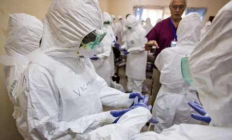 A World Health Organization, WHO, worker, right rear, trains nurses to use Ebola protective gear in Freetown, Sierra Leone.