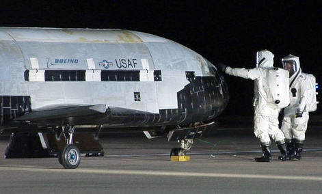Technicians examining the X-37B unmanned spaceplane shortly after landing Friday Dec. 3, 2010 at Vandenberg Air Force Base, Calif.