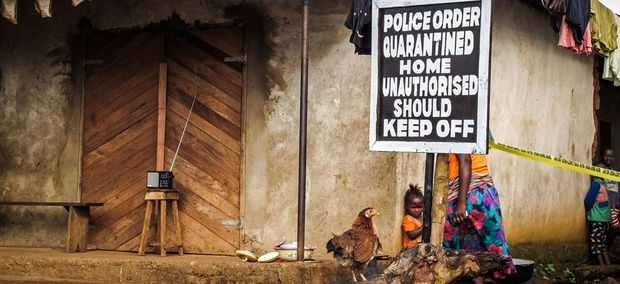 A child, center, stands underneath a signboard reading 'Police order quarantined home unauthorised should keep off' as a family home is placed under quarantine due to the Ebola virus in Port Loko, Sierra Leone.