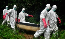 A burial team in protective gear carry the body of woman suspected to have died from the Ebola virus in Monrovia, Liberia.