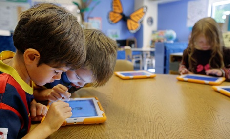 Aiden Crott, center, helps Daniel Hernadez with his ScratchJr iPad program while Talia Levitt, right, works with hers at the Eliot-Pearson Children's School in Medford, Mass. Researchers created the app that teaches basic computer programming to children