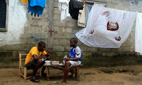 Mohammed Kromah, left, 26, and his half-brother Michell Pratt listen to election results on the radio of a cell phone while eating lunch outside their house in the Sinkor neighborhood of Monrovia, Liberia.