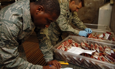 Senior Airman Kendall Thomas, 379th Expeditionary Medical Group Blood Trans-shipment Center laboratory technician, and Maj. Brian Dart, 379th MDG BTC chief, verify blood products before shipment.