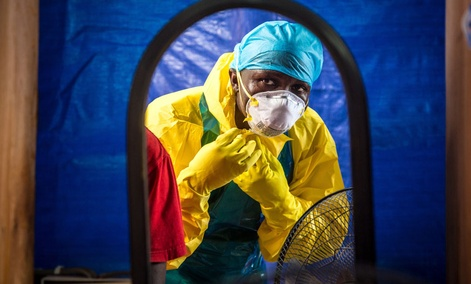 A healthcare worker dons protective gear before entering an Ebola treatment center in the west of Freetown, Sierra Leone.