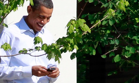 President Barack Obama uses his BlackBerry device as he walks at Sidwell Friends school in Bethesda, Md.