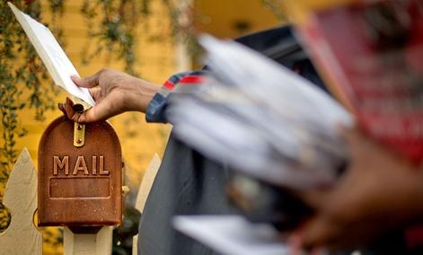U.S. Postal Service letter carrier, Jamesa Euler, delivers mail, in Atlanta.