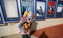 "A poster for the movie ""The Interview"" is carried away by a worker after being pulled from a display case at a Carmike Cinemas movie theater, Wednesday, Dec. 17, 2014."