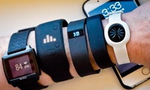 Various fitness trackers are posed for a photo next to an iPhone, Monday, Dec. 15, 2014.