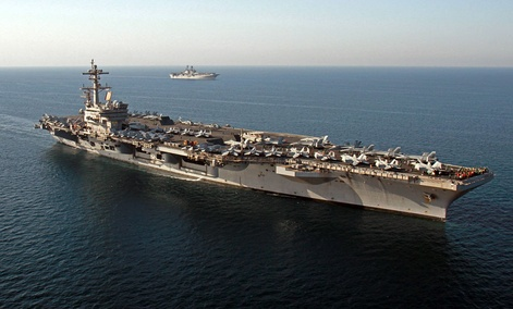 The amphibious assault ship USS Makin Island, background, pulls alongside the aircraft carrier USS George H.W. Bush in the Persian Gulf.