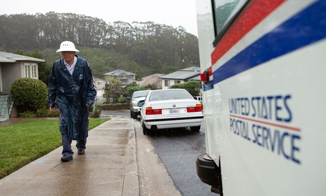 Danny Joe delivers mail as it rains in San Bruno Calif., on Thursday, Dec. 11, 2014. Joe has worked for the United States Postal Service for twenty years.