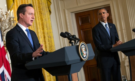 President Barack Obama listens as British Prime Minister David Cameron speaks during their joint news conference in the White House.